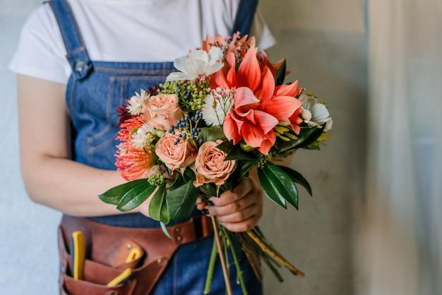 Женщина делает букет из свежих садовых пионов. создание весеннего букета с красными и оранжевыми цветами. флорист и декоратор Premium Фотографии