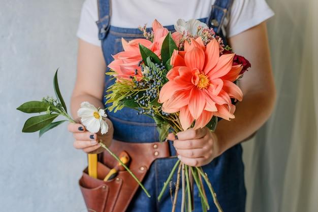 Женщина делает букет из свежих садовых пионов. создание весеннего букета с красными и оранжевыми цветами. Premium Фотографии