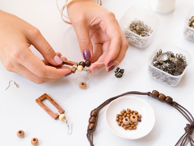 Woman making accessories with wooden beads Free Photo