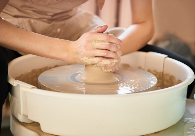 Woman making ceramic pottery on wheel, creation of ceramic ware. Premium Photo