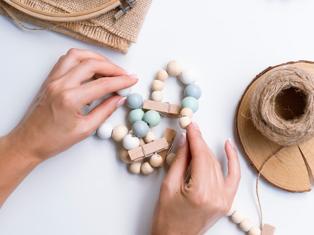 Woman making decorations with wood beads Free Photo