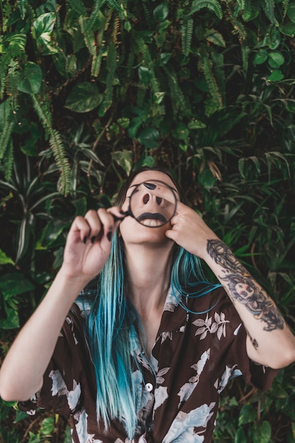 Woman making funny face through a magnifying glass Free Photo
