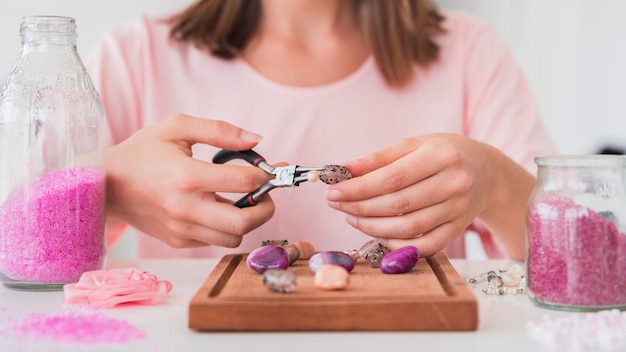 Woman making handmade jewelry with beads Free Photo