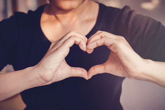 Woman making hands in heart shape sign, health insurance, donation volunteer concept Premium Photo