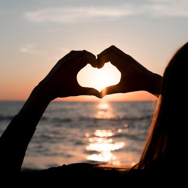 Donna che fa un cuore al tramonto Foto Gratuite