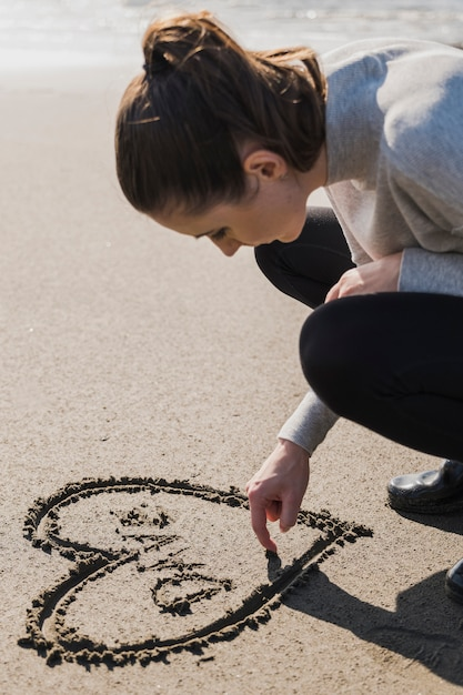 Woman making heart on wet sand Free Photo