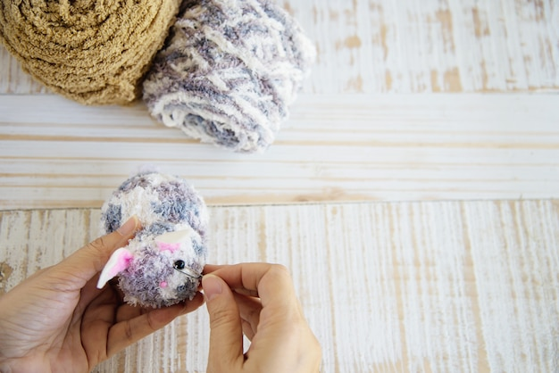 Woman making lovely bunny doll from yarn  - easter holiday celebration concept Free Photo