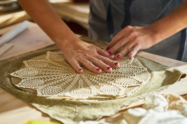 Woman making pattern on ceramic plate, hands close-up, Premium Photo