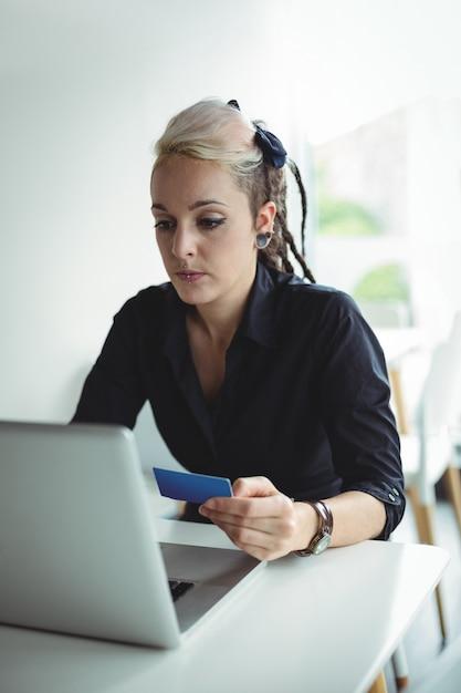 ノートパソコンとクレジットカードを使用してオンラインで支払いを行う女性 無料写真