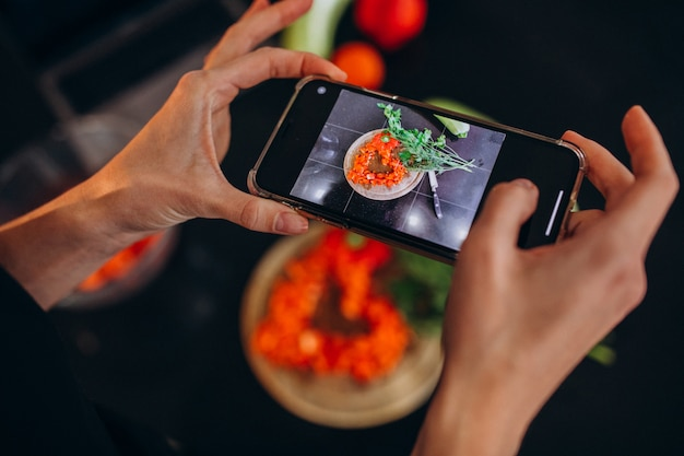 Woman making photo of a meal on her phone Free Photo