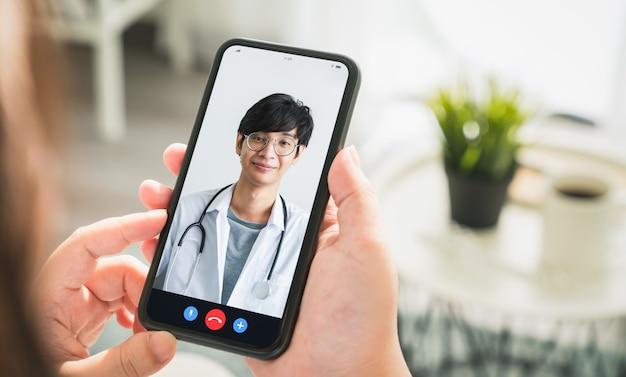 Женщина делает видеозвонок врачу на смартфоне и предоставляет онлайн-консультации. Premium Фотографии