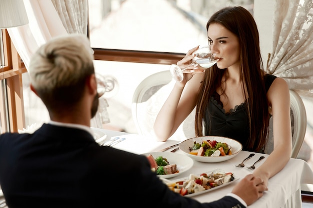 Woman and a man are holding hands on a romantic date at the restaurant Free Photo