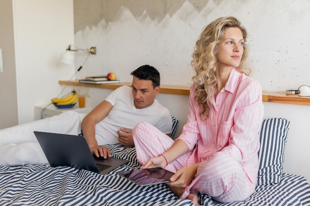 Woman and man in bed in morning smiling happy working online, family living together in bedroom wearing pajamas Free Photo