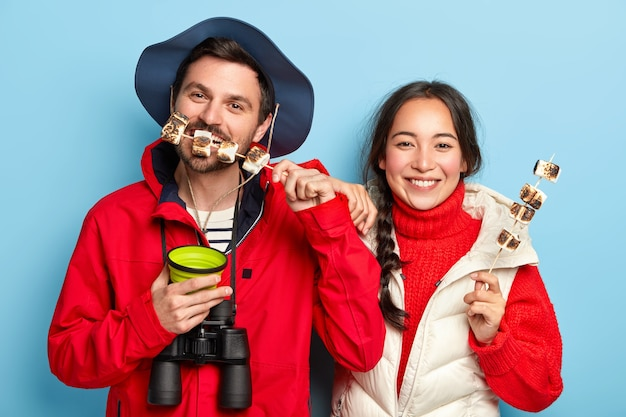 Woman and man eat roasted marshmallows made on camping fire, have picnic in forest, enjoy leisure, drink hot bevereage, wears casual outfit, pose against blue wall Free Photo
