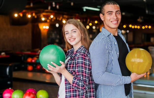 Donna e uomo che tengono le palle da bowling colorate Foto Gratuite