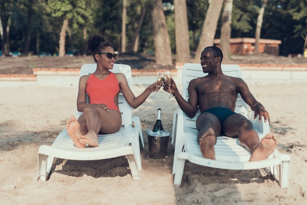 Woman and man is drinking champagne on sandy river beach Premium Photo