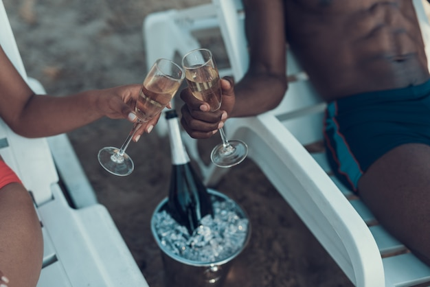 Woman and man is toasting of glasses with champagne on beach Premium Photo