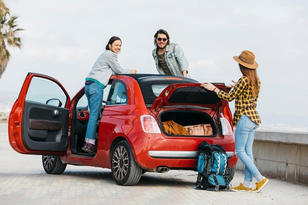 Woman and man leaning out from car near lady with backpack near car trunk Free Photo