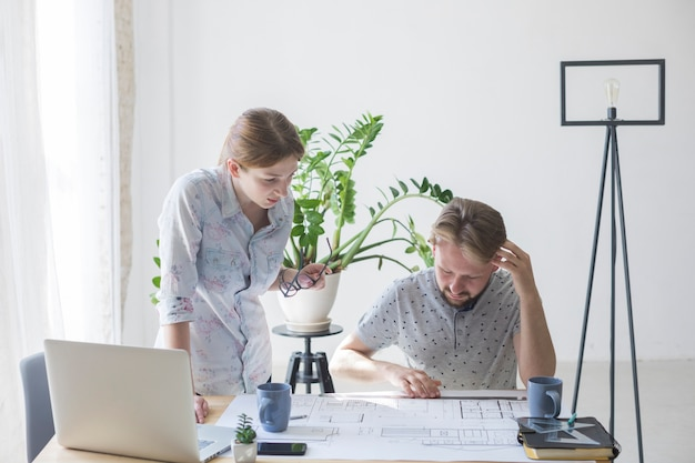 Woman and man looking at blueprint while working in office Free Photo