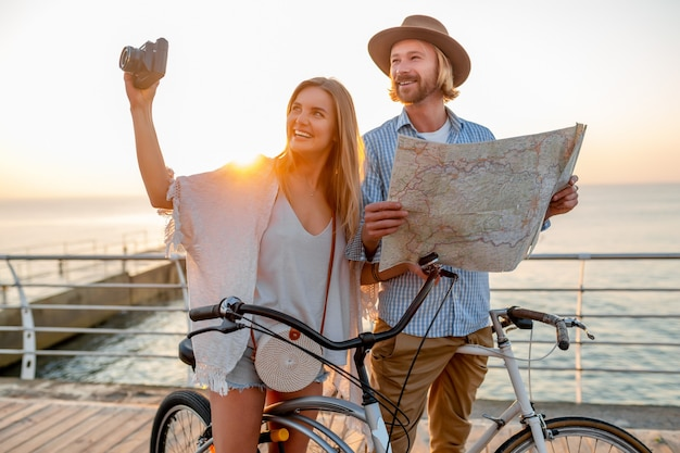 Woman and man in love traveling on bicycles at sunset sea Free Photo