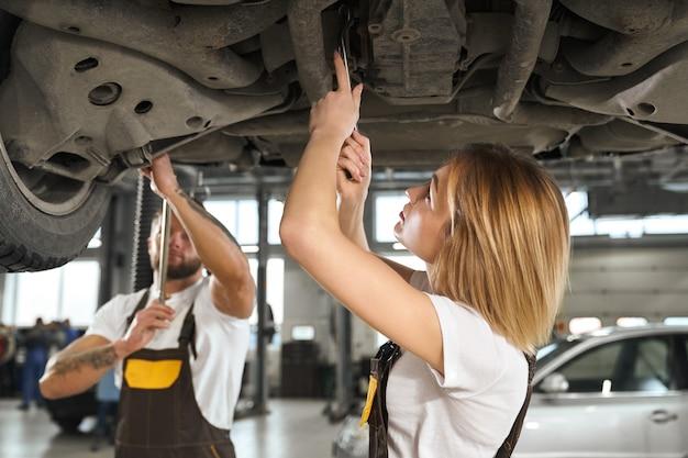 Woman and man mechanics repairing car undercarriage. Free Photo