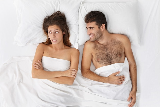 Woman and man sitting in bed top view Free Photo