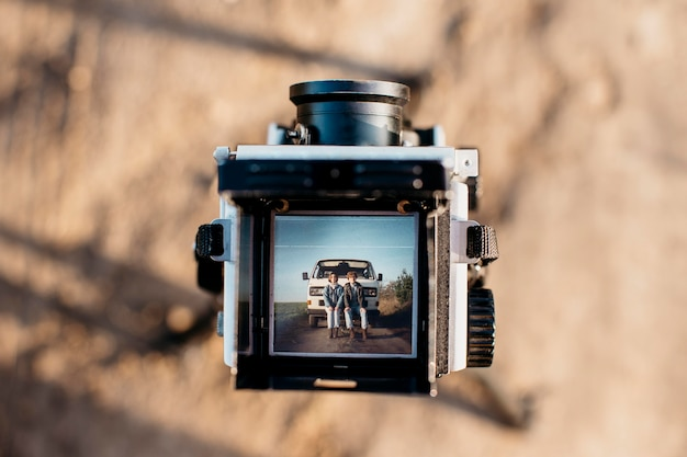 Woman and man sitting on a van in a retro camera Free Photo