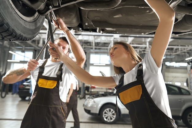 Woman and man working in autoservice as mechanics. Free Photo