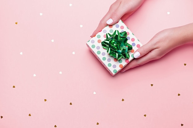 Woman manicured hands holding green giftbox on pastel pink background with confetti Premium Photo