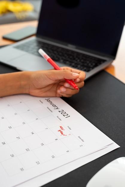 Woman marking january first on a calendar Premium Photo