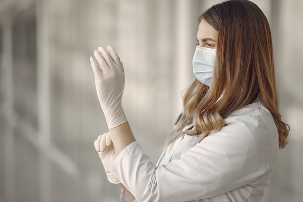 Woman in a mask and uniform puts on gloves Free Photo