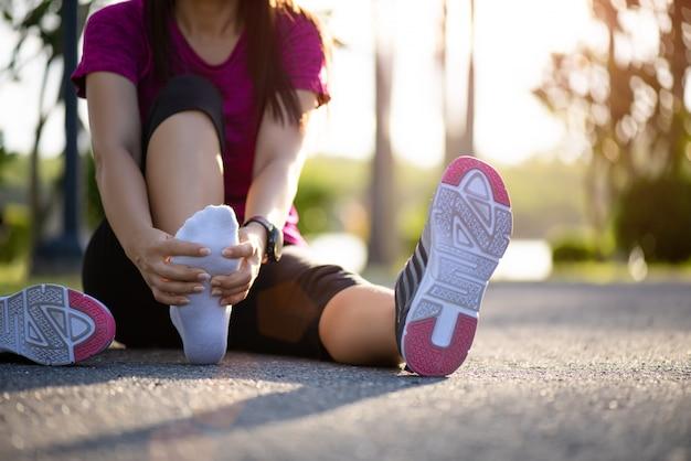 Premium Photo   Woman massaging her painful foot while exercising. running  sport injury.