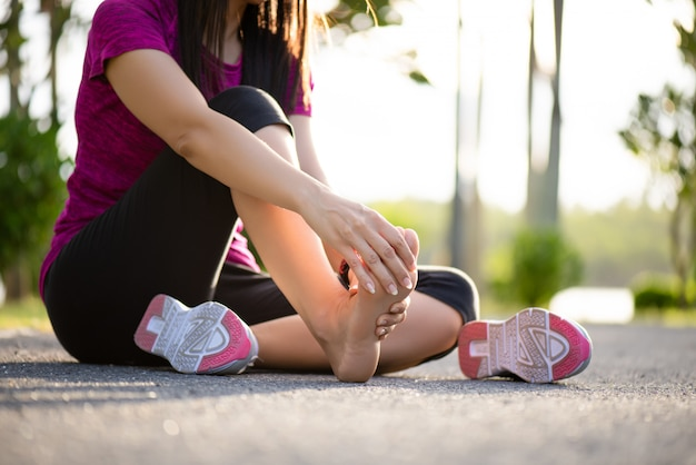 Woman massaging her painful foot while exercising. Premium Photo