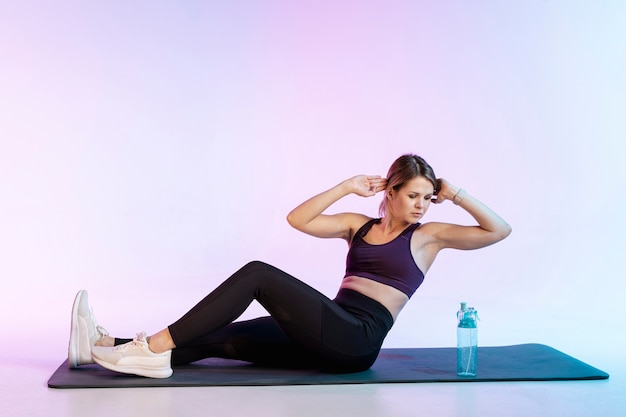 Woman on mat doing abdominal exercise Free Photo