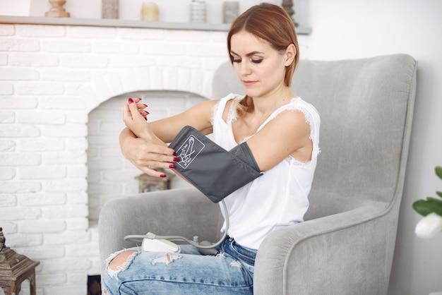 女性は自宅で自分の圧力を測定します 無料写真