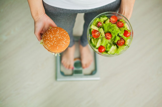 Woman measuring body weight on weighing scale holding burger and salad, sweets are unhealthy junk food, dieting, healthy eating, lifestyle, weight loss, obesity, top view Premium Photo