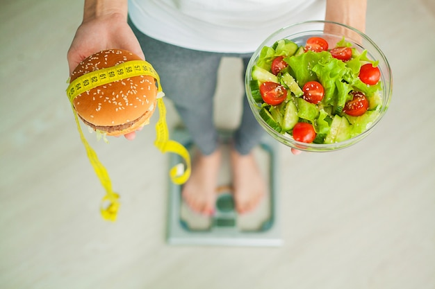 Woman measuring body weight on weighing scale holding burger and salad. Premium Photo