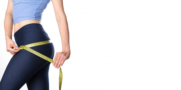 Woman measuring her body. fitness woman banner. copy space. Premium Photo
