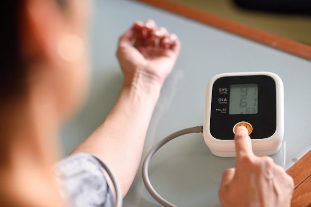 Woman measuring her own blood pressure at home. Premium Photo