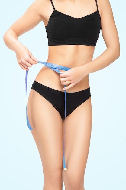 Woman measuring her waist by blue measure tape Premium Photo