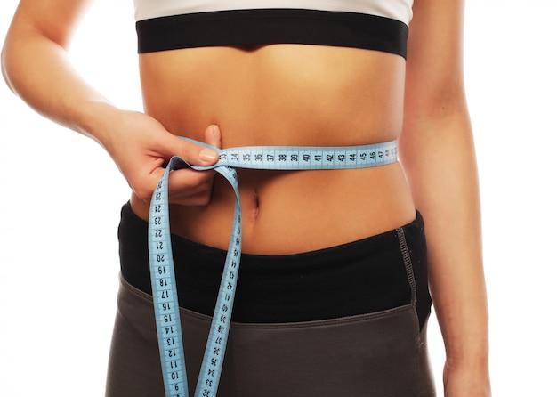 女性は彼女のウエストを測定します。パーフェクトスリムボディ。白で隔離されます。 Premium写真