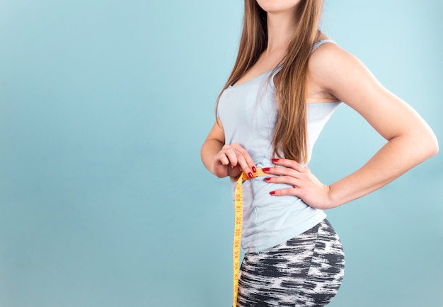 Woman measuring waist with tape 23 2148035055