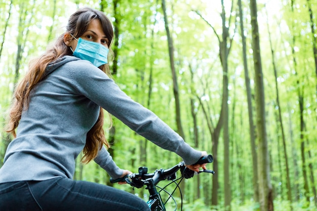 Woman in medical mask rides a bicycle in the park | Premium Photo