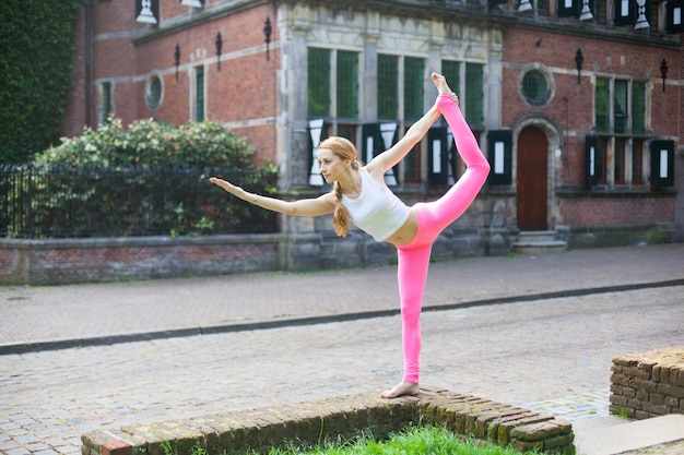 Woman  meditating and doing yoga asana exercisers in city street Premium Photo