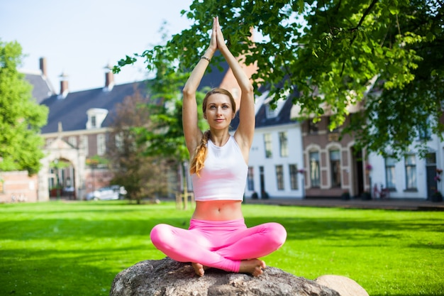 Woman  meditating and doing yoga asana exercisers in park Premium Photo