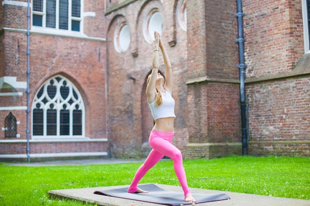 Woman  meditating and doing yoga exercisers in city street Premium Photo