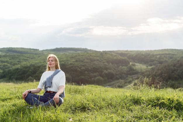 Женщина медитирует на природе Premium Фотографии