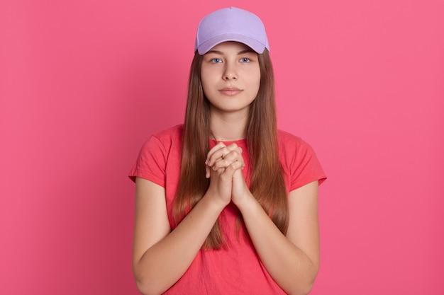両方の手のひらに加わって瞑想する女性、カメラ目線、カジュアルなtシャツと野球帽を着用 無料写真