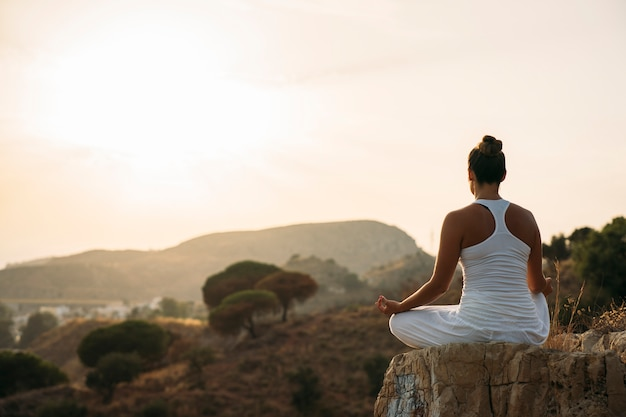 Woman meditating in the mountainside Free Photo