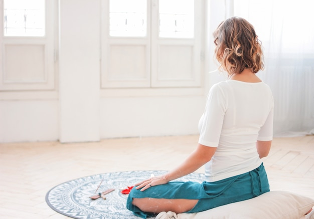 Woman meditating practicing yoga in front of candles and red rose petals, view from back Premium Photo